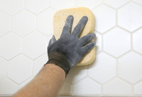 Clean excess tile grout with a sponge